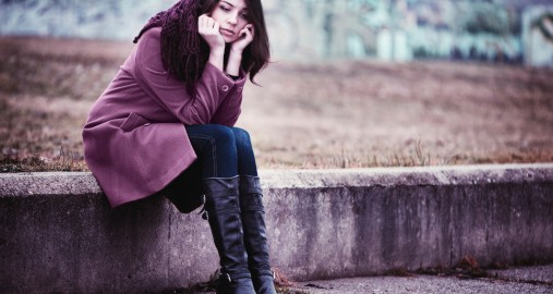image of a woman sitting outside on a concrete ledge