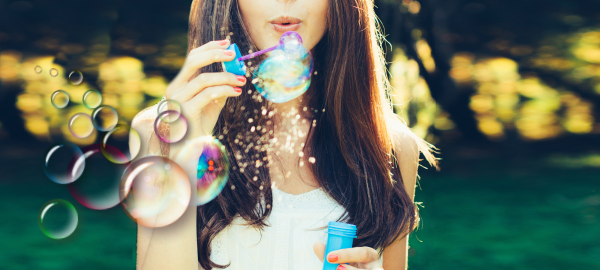 Photo-of-a-happy-girl-blowing-bubbles