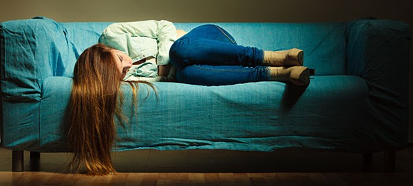 Woman lying on couch struggling with depression