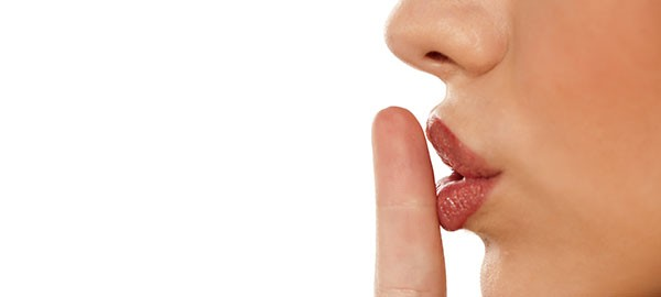 woman holding finger to her lips