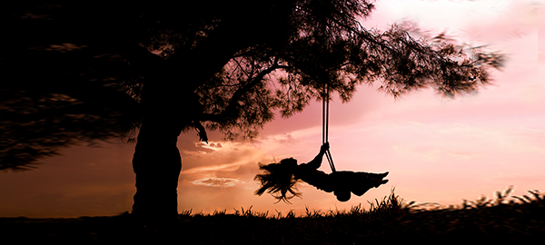 silhouette-of-joyful-woman-on-a-swing-with-sunset