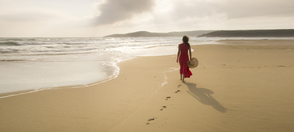woman-walking-on-sand-beach-leaving-footprints