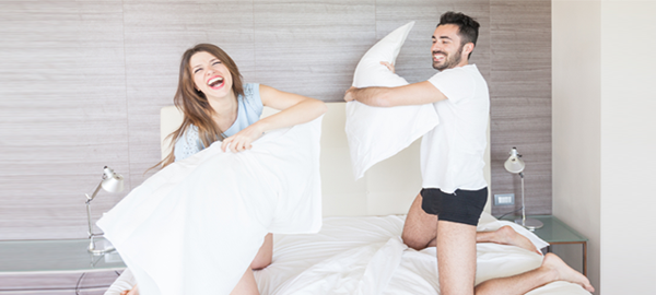 happy-couple-having-pillow-fight